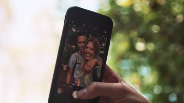 Lächelnde Paarung nimmt Selfie im Wald