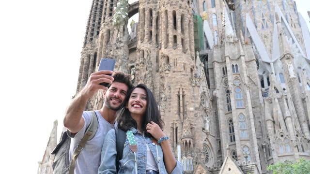 smiling couple taking selfie in front of sagrada familia - photography themes stock videos & royalty-free footage