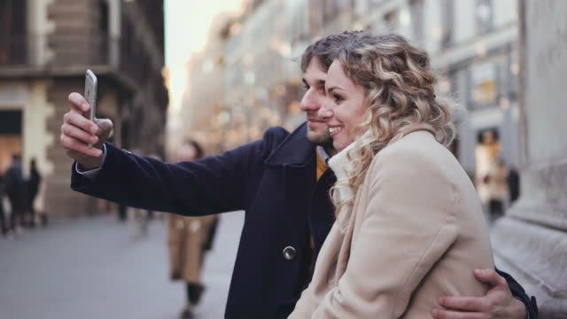 vidéos et rushes de smiling couple taking selfie in old town, florence, italy - photophone