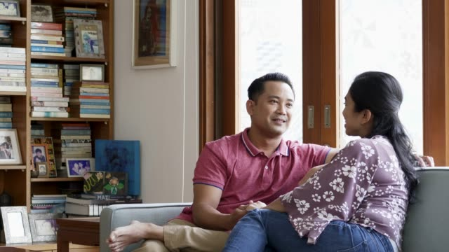 smiling couple talking while sitting on sofa - malaysian ethnicity stock videos & royalty-free footage