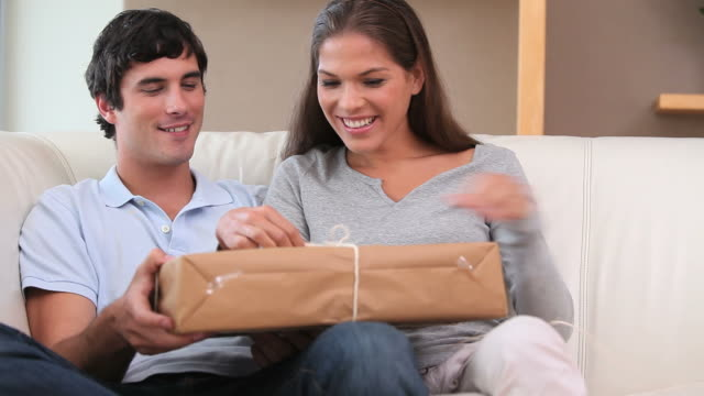 Smiling couple unwrapping a gift