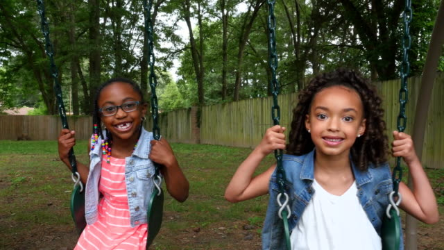 ms smiling cousins sitting on swings in backyard of home - braided hair stock videos & royalty-free footage