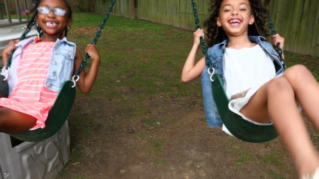 vidéos et rushes de ms smiling cousins swinging on play set in backyard of home - balançoire