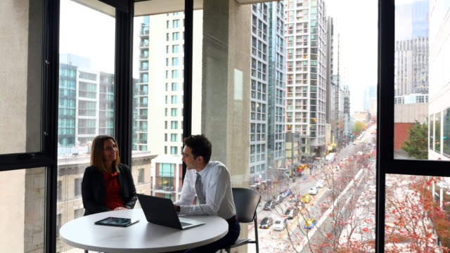 MS Smiling coworkers in discussion in office with view of city