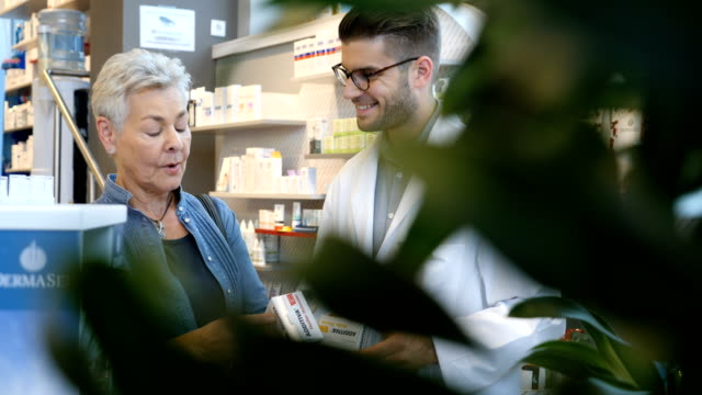 lächelnde kunden diskutieren mit chemiker im store - apothekerberuf stock-videos und b-roll-filmmaterial