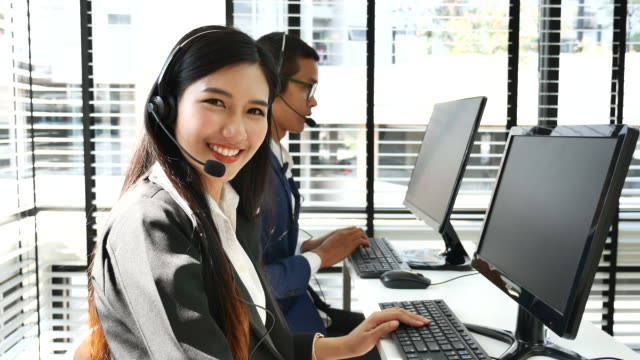 Smiling Customer support phone operator using headsets, Looking at camera