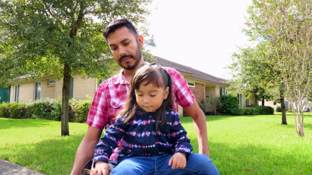 ms smiling daughter sitting in fathers lap in wheelchair while out in neighborhood on sunny afternoon - persons with disabilities stock videos & royalty-free footage