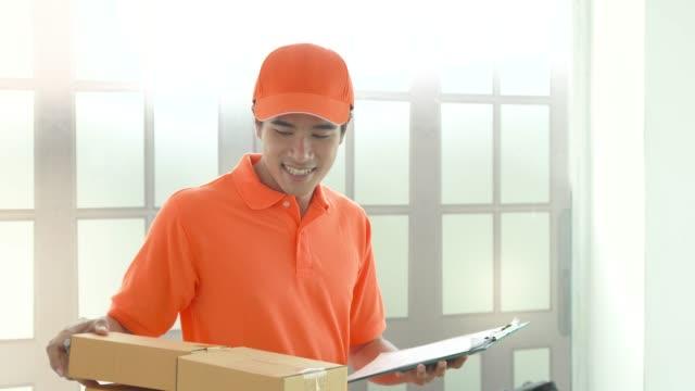 vídeos y material grabado en eventos de stock de sonriente entrega hombre manos sobre la caja, hombre en uniforme de servicio - haz de luz