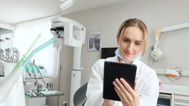 lächelnde zahnarzt arbeitet an tablet - zahnarzt stock-videos und b-roll-filmmaterial