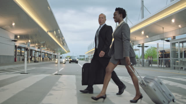 smiling diverse business partners walk through crosswalk towards airport terminal. - geschäftsreise stock-videos und b-roll-filmmaterial