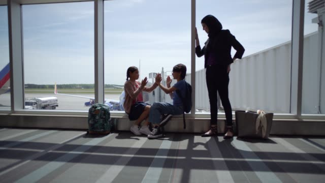 vidéos et rushes de slo mo. smiling diverse young brother and sister play pat-a-cake at terminal gate while mother looks on. - avion de tourisme