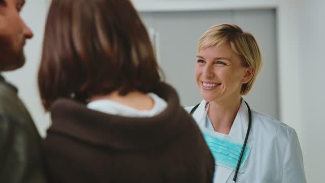 lächelnder arzt diskutiert mit paar im krankenhaus - vertrauen stock-videos und b-roll-filmmaterial