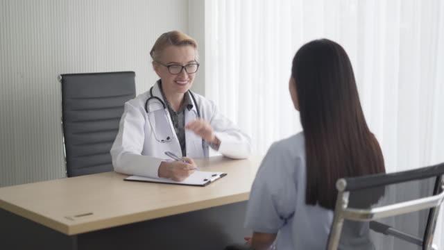 leende läkare rekommendera kvinnlig patient på skrivbord sjukhus rum - luta sig tillbaka bildbanksvideor och videomaterial från bakom kulisserna