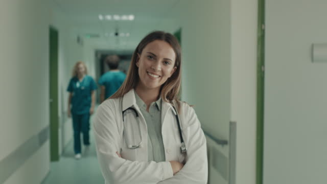 smiling doctor standing arms crossed at hospital - arms crossed stock videos & royalty-free footage