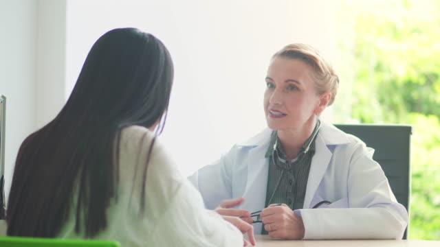 医師が女性患者に話して笑って、ドリー ショット - 女性患者点の映像素材/bロール
