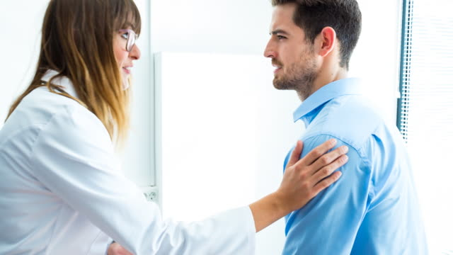 CU smiling doctor talking to relieved patient at clinic