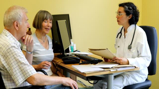 Smiling doctor talking to senior couple at desk