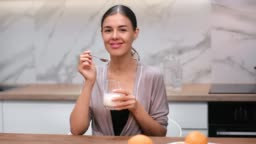 Smiling domestic woman eating yogurt from transparent glass. Shot on RED Raven 4k Cinema Camera