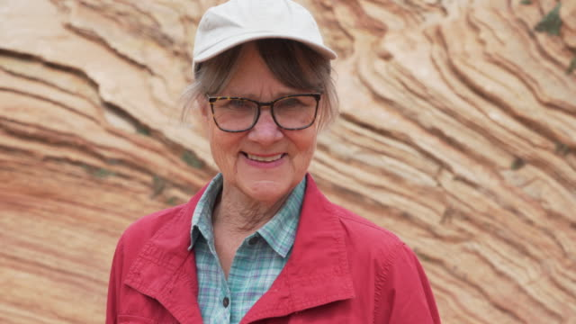 smiling elderly woman looking at camera in front of rocky sandstone cliff - sandstone stock videos & royalty-free footage