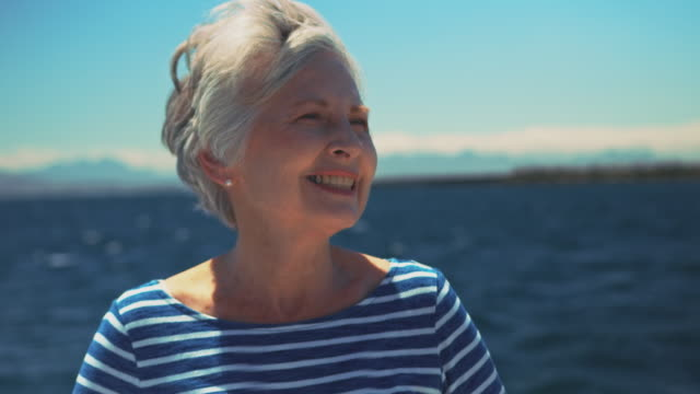 smiling elderly woman steering yacht in vacation - senior women stock videos & royalty-free footage