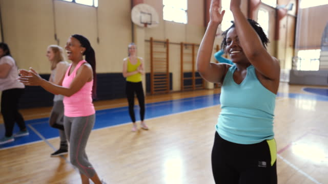 Smiling, enthusiastic people cheering in dance class