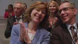 Smiling entrepreneurs applauding during seminar