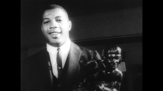 / a smiling ernie davis accepts the heisman trophy / cu on the trophy and the plaque details / footage of davis as number 44 playing football for... - syracuse stock videos & royalty-free footage