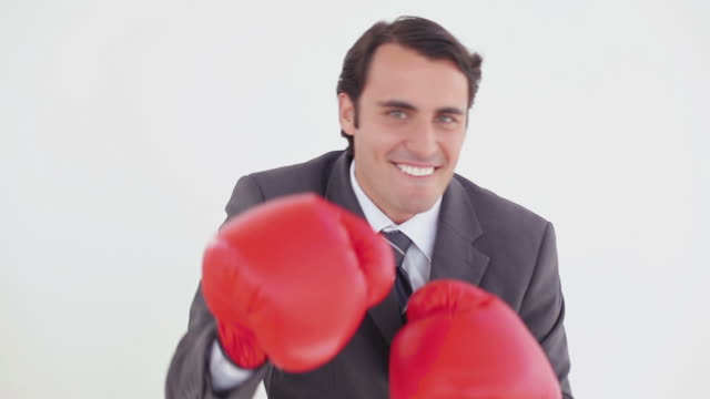 Smiling executive boxing with red gloves