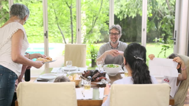 smiling family clapping as asado platter is brought to table - happy meal stock videos & royalty-free footage