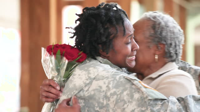 smiling family hugging woman in military uniform - military uniform stock videos & royalty-free footage