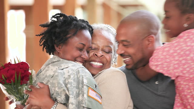 smiling family hugging woman in military uniform - army stock-videos und b-roll-filmmaterial