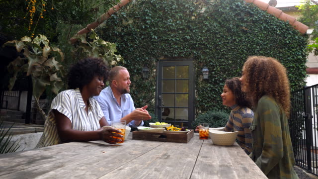 ms smiling family in discussion during backyard picnic - pre adolescent child stock videos & royalty-free footage
