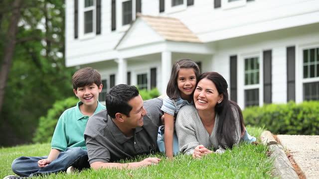 stockvideo's en b-roll-footage met glimlachende familie die in gras legt en camera voor huis bekijkt - voor of achtertuin