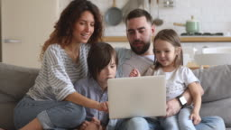 Smiling family of four using laptop, shopping at home.