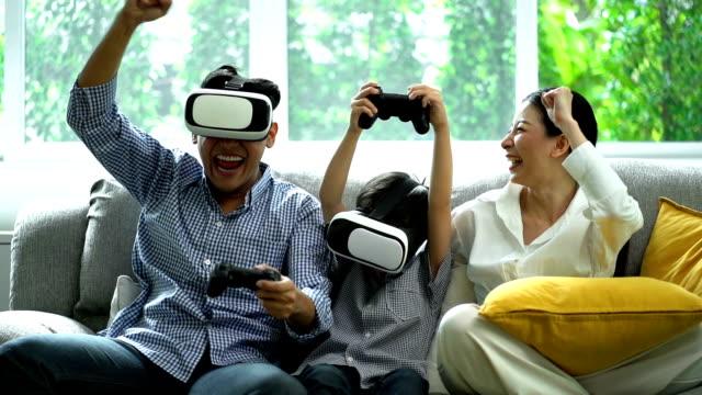 リビングルームでバーチャルリアリティシミュレータメガネを使用しながら、ゲームに勝った後に手を上げる笑顔の家族 - 仮想空間点の映像素材/bロール