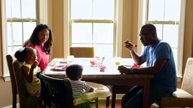 MS Smiling family sitting together at dining room table eating breakfast