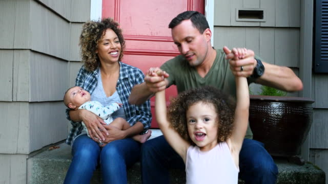ms smiling family sitting together on front porch on summer evening - family with two children stock videos & royalty-free footage