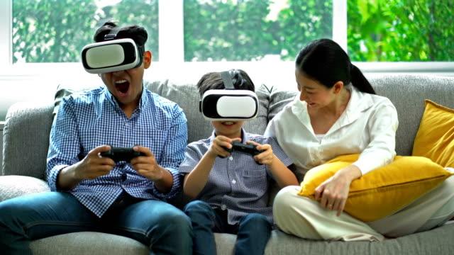 リビングルームで一緒にvrヘッドセットを使用して4k笑顔の家族 - ゲーム点の映像素材/bロール