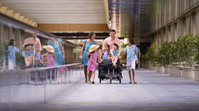 smiling family walking with baggage cart in airport - 荷物点の映像素材/bロール