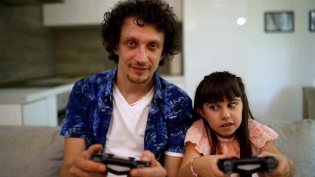 vídeos y material grabado en eventos de stock de sonriendo padre e hija jugando videojuego en casa - analógico