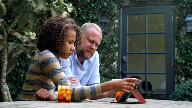 ms smiling father and daughter watching video on digital tablet in backyard - 12 13 jahre stock-videos und b-roll-filmmaterial