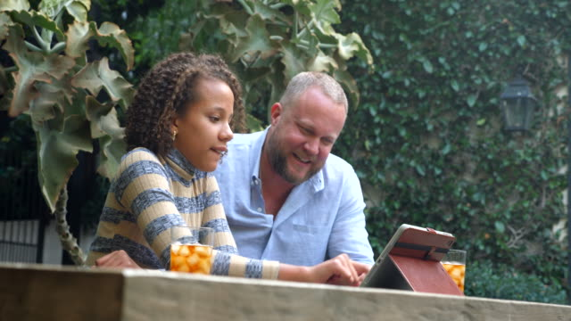 ms smiling father and daughter watching video on digital tablet in backyard - differential focus stock videos & royalty-free footage