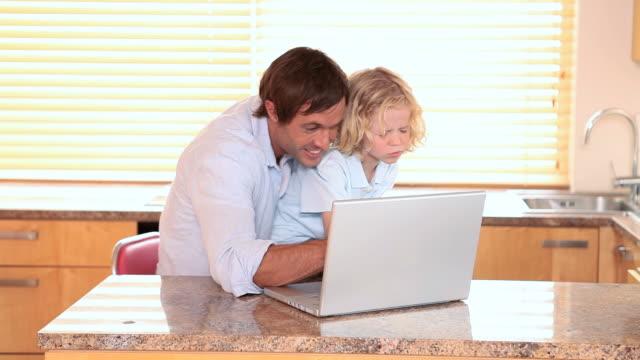vídeos de stock e filmes b-roll de smiling father and son using a laptop - colo