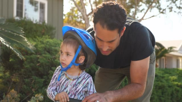 vidéos et rushes de ms smiling father encouraging young daughter riding scooter on sidewalk - casque de vélo