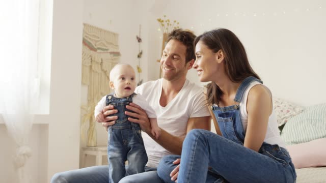 Smiling father holding aloft son by woman at home