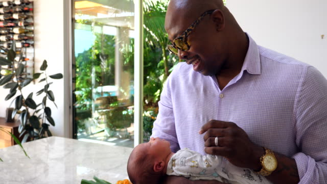 ms smiling father holding newborn son in kitchen - genderblend stock videos & royalty-free footage