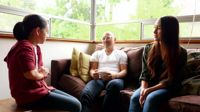 MS Smiling father in discussion with daughters in living room before school