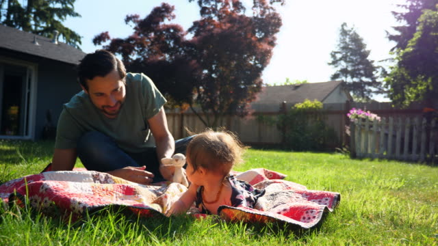 MS Smiling father playing with infant daughter while lying on blanket in backyard