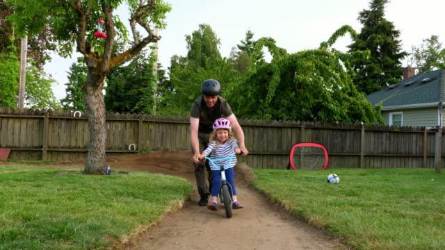 vídeos y material grabado en eventos de stock de pan smiling father pushing laughing daughter on bicycle on backyard dirt track on summer evening - familia con cuatro hijos