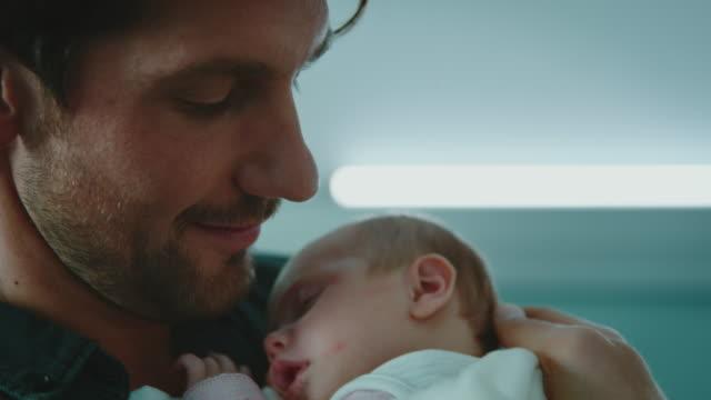 vídeos de stock, filmes e b-roll de pai de sorriso com o bebê de sono no hospital - família de duas gerações